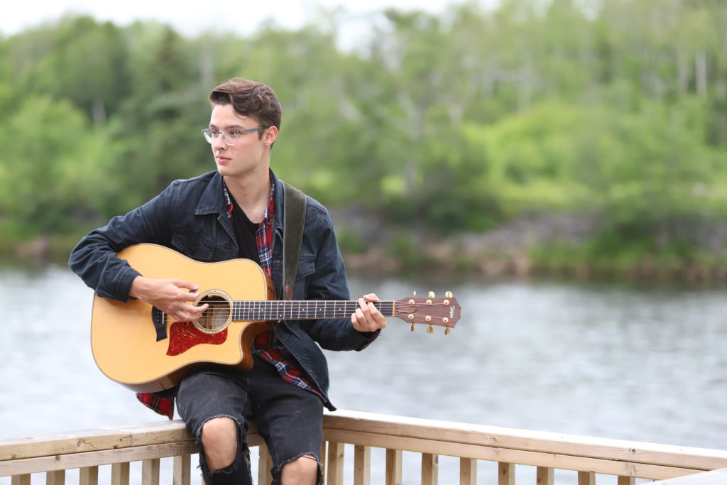 Cameron Molloy sitting near the water with a guitar